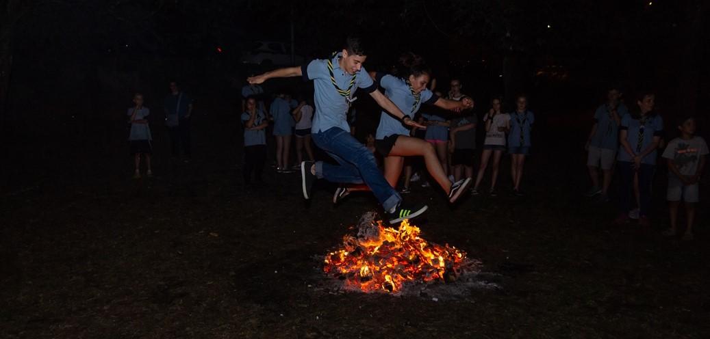 rapaces e rapazas scouts saltando o lume